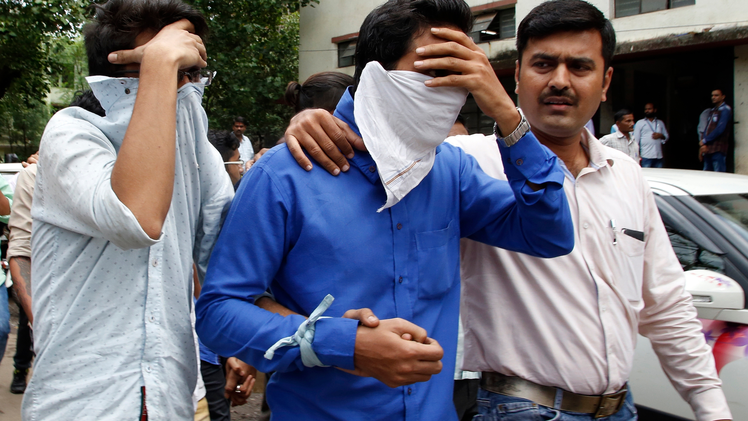 A police official, right, escorts two men outside the court in Thane, outskirts of Mumbai, India, Thursday, Oct. 6, 2016. Indian police have ar_191818