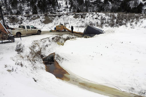 This Dec. 10, 2016 photo provided by the North Dakota Department of Health shows a cleanup crew at the site of oil spill from the Belle Fourche Pipeline that was discovered Dec. 5 in Ash Coulee Creek, a tributary of the Little Missouri River, near...