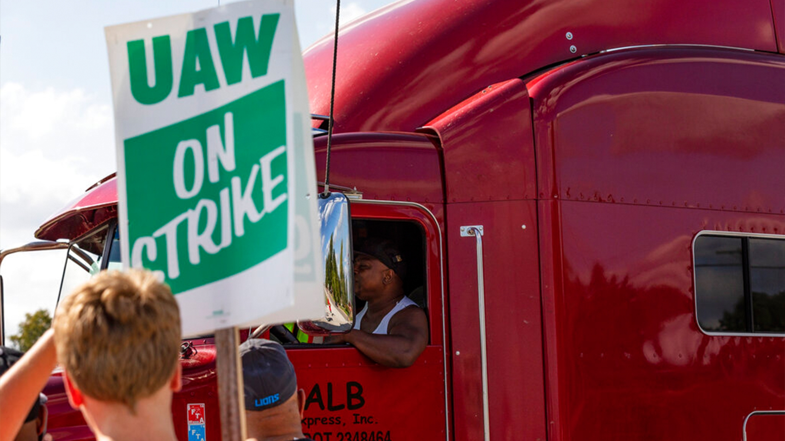 A semi-truck driver entering the GM Davison Road Processing Center in Burton passes union members striking. United Automobile Workers remain on strike against GM on Tuesday, Sept. 17, 2019 in Burton, Mich. (Sara Faraj/The Flint Journal via AP)