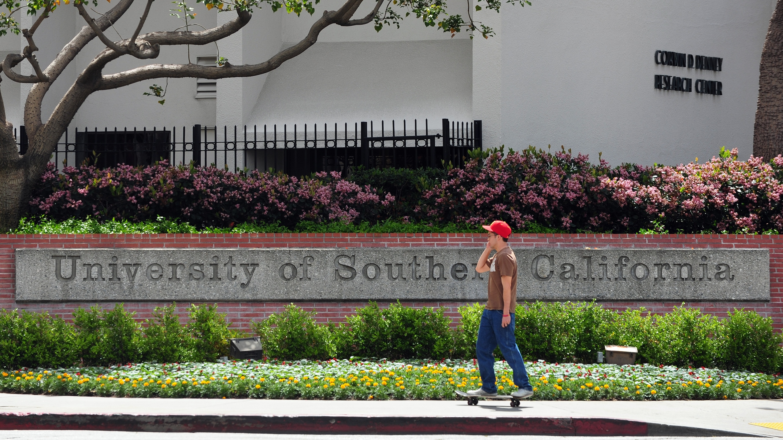 A student rides his skateboard past an e