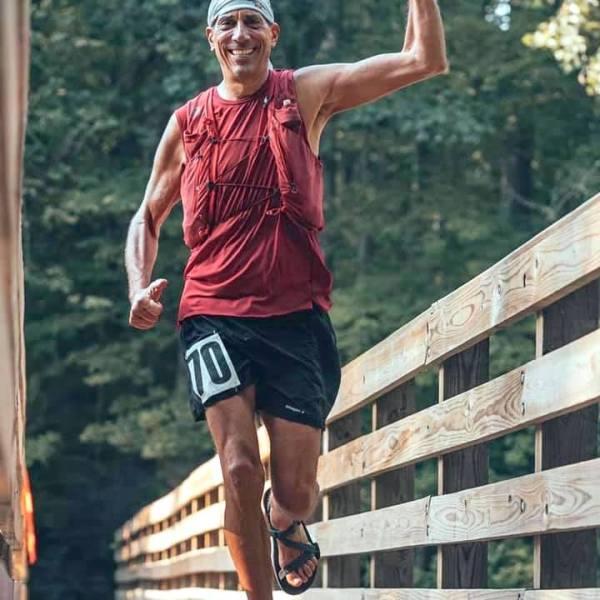 Man in red shirt, black shorts running marathon outdoors